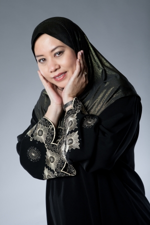 Young Muslim Malay woman in black hijab with hands over her face  photo