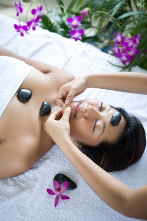 body massage: Young woman receiving body massage from therapist Stock Photo