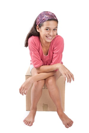 laborious: Young girl sitting on empty cardboard box  Stock Photo