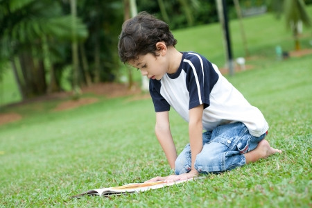 Young boy enjoying his reading book in outdoor park Stock Photo - 14688781