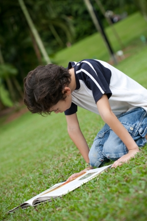 Young boy enjoying his reading book in outdoor park Stock Photo - 14682992
