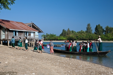 ferrying: NGWE SAUNG MYANMAR- FEBRUARY 1st  Local people cross rivers daily in the west coast of Myanmar to get to place due to numerous rivers in the delta region  River boat  ferrying school children and villagers, Ngwe Saung Myanmar, February 1st 2010