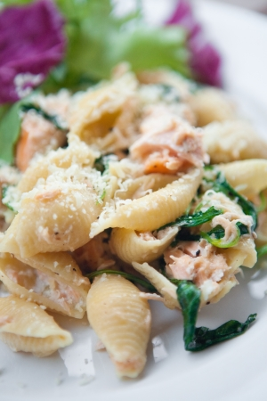 Pasta with salmon, spinach and cream, with fresh salad on the side  photo