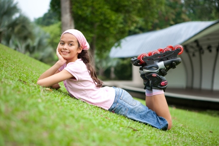 Beautiful young girl resting after rollerblading in the park photo
