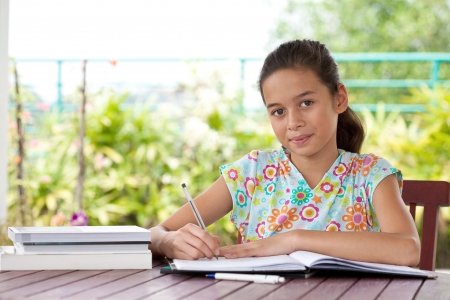 Beautiful young girl doing her homework in a home environment photo