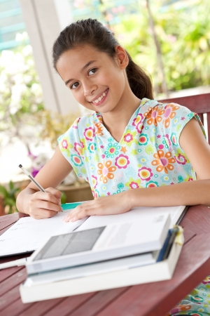 Beautiful young girl doing her homework in a home environment Stock Photo - 14688954