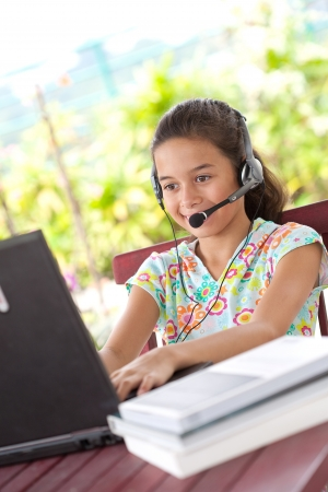online safety: Young girl with headset and using the laptop computer, on the outdoor terrace