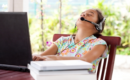 Young girl listening to headphone while on laptop computer, resting her head on chair. Banque d'images