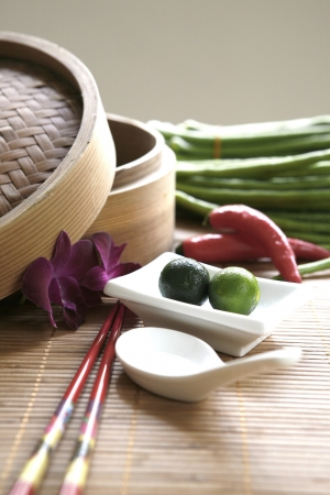 local supply: Chinese cooking set with oriental ingredients  of long beans, chili and local limes. Stock Photo