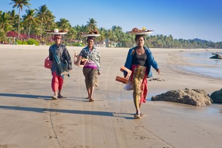 NGWE SAUNG MYANMAR - 2ND FEBRUARY. Three local Burmese women selling grilled fish to visitors along the beach of Ngwe Saung, Myanmar 2nd February 2010. The west coast of Myanmars boast the most  beautiful sandy beaches and very popular amongst locals and