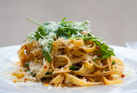 Delicious fettucine pasta with sundried tomato and rocket leaves  photo