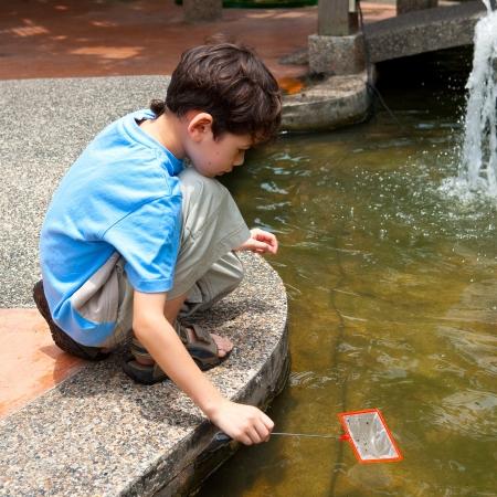 Young boy enjoying catching fish