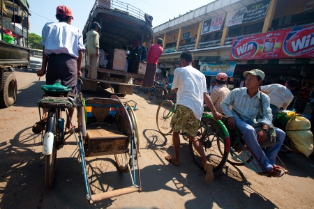 frame less: PATHEIN MYANMAR - JAN 30. Trishaw operator ferrying locals from market, 30 Jan 2010, Pathein, Myanmar. The most common method of transport for the local people for short trips. Editorial