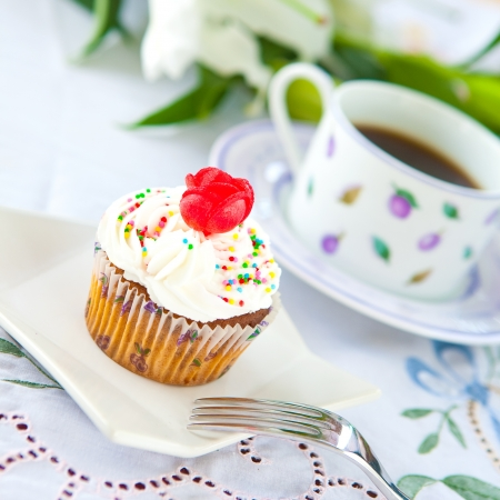 garnishing: Pretty cupcake with a cup of coffee Stock Photo