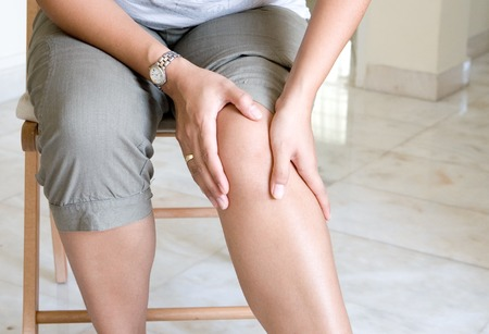 human body substance: Woman suffering from pain in knee joint. Stock Photo