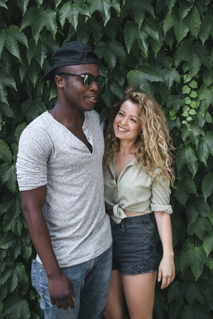 afecto: caucasian and african american couple have fun between green leafs