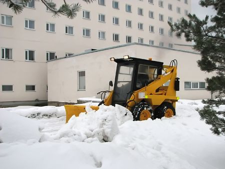 Yellow tractor shoveling the snow. photo