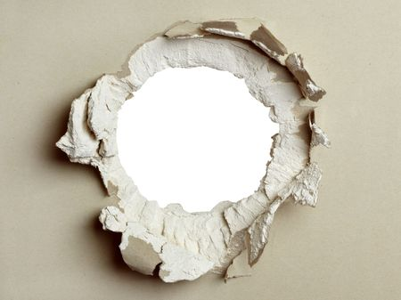 Hole in the grey plasterboard with uneven edges.