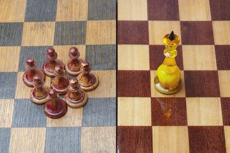 inequality: Luxirious chess king opposing shabby pawns in concept of social inequality.