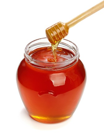 Wooden dipper with jar of honey, isolated on the white background