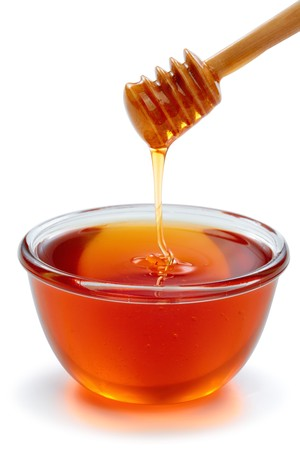 Wooden dipper with bowl of honey, isolated on the white background photo