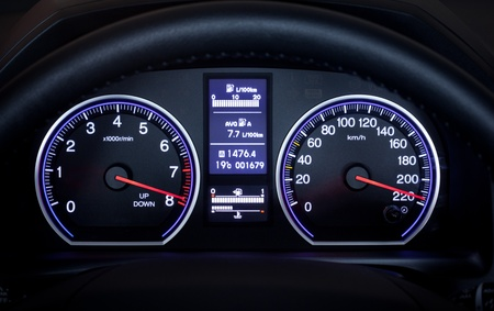 Illuminated car dashboard displaying maximum speed.