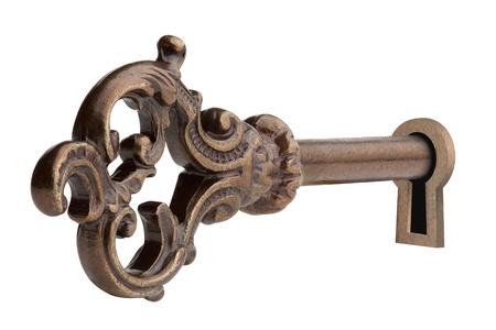 Vintage sleutel in sleutelgat, geïsoleerd op de witte achtergrond, uitknippad opgenomen. Stockfoto