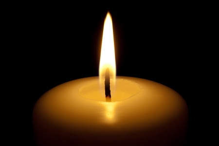 Burning candle, isolated on the black background. photo