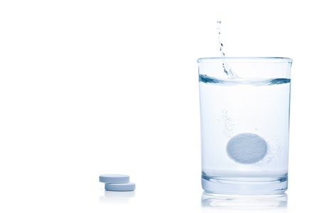 Fizzy pill splash in a glass of water, isolated on the white background,  Standard-Bild