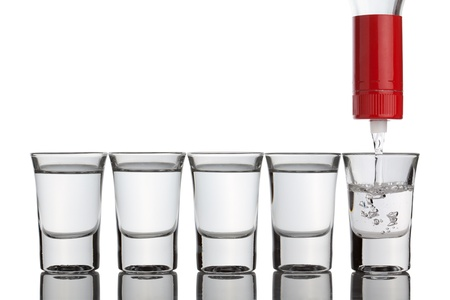 sparo: Vodka versando in bicchierini in piedi in fila, isolato su sfondo bianco