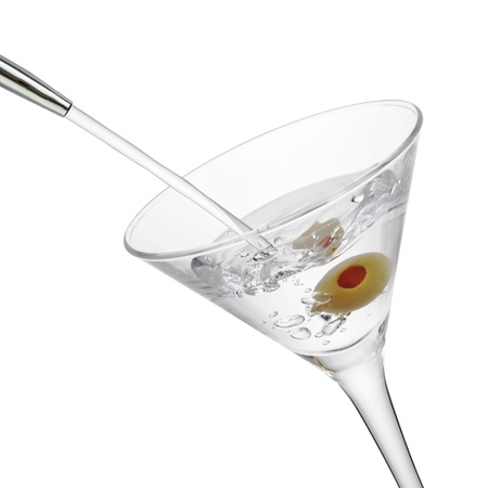 gin: Alcohol pouring into a martini glass with olive, isolated on the white background, clipping path included