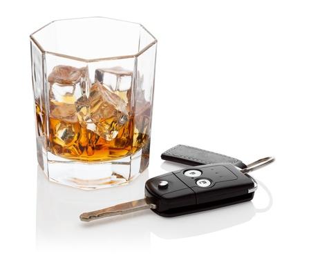 Glas whisky en autosleutels, geïsoleerd op de witte achtergrond, het knippen inbegrepen weg