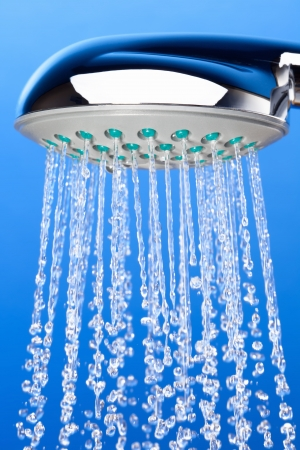 Shower with falling drops of water on the blue background
