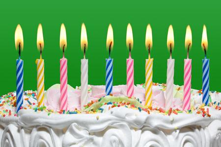 velitas de cumpleaños: Torta de cumpleaños con velas de colores sobre el fondo verde