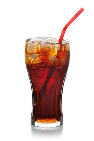 ESTLAND-JULI 09, 2014 Coca-Cola met ijsblokjes en stro in een glas, geïsoleerd op de witte achtergrond, het knippen inbegrepen weg