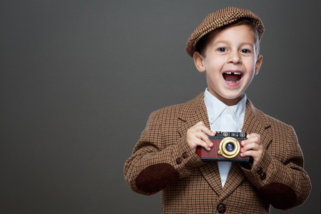 blazer: Cute boy with vintage photo camera on the grey background. ( Retro style.)
