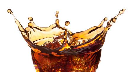 Splash de cubitos de hielo en un vaso de refresco de cola, aislado en el fondo blanco, camino de recortes incluido.