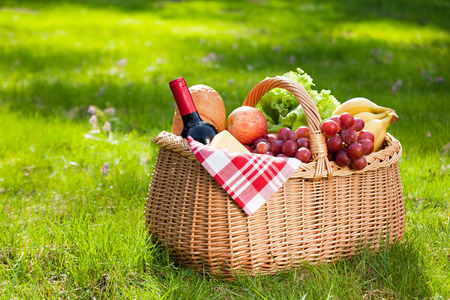 fruits in a basket: Picnic basket with food on green sunny lawn.