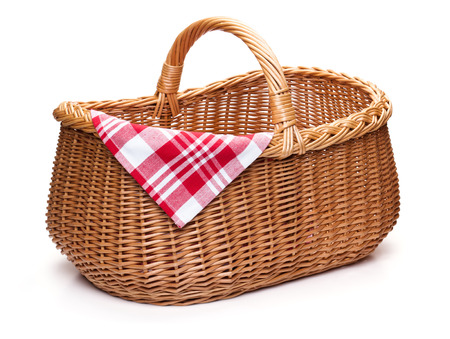 Wicker picnic basket with red checked napkin isolated on the white background.