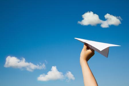 Paper plane in child hand on blue sky and clouds background. (With space for text.) Archivio Fotografico