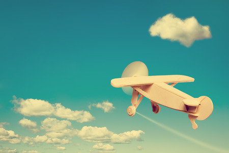 Wooden plane flying in the sky, with space for text.
