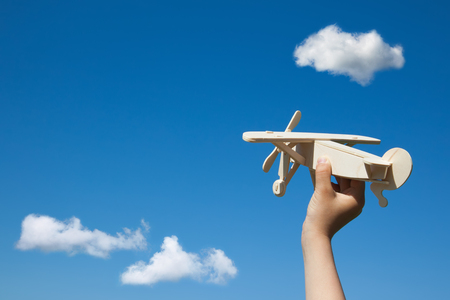 Wooden plane in child hand on the blue sky and clouds background. ( With space for text.) Archivio Fotografico