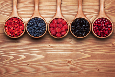 Various wild berries in small scoops on the wooden table. Background with space for text. Archivio Fotografico
