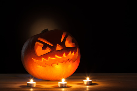 Halloween pumpkin with three candles on wooden table. Archivio Fotografico