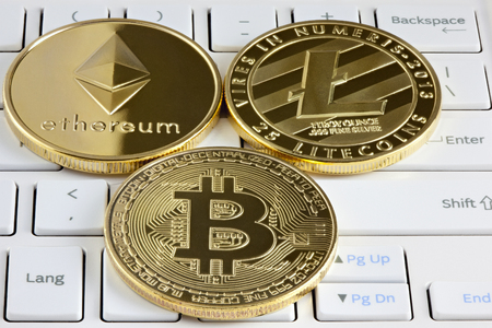 Physical golden bitcoin, ethereum and litecoin coin lying on computer keyboard. Archivio Fotografico