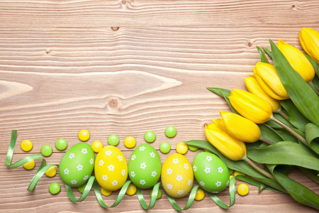 Easter eggs, chocolate candies and yellow tulips on wooden background. Archivio Fotografico
