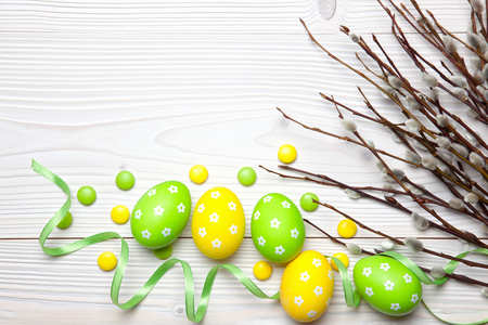 Easter eggs, chocolate candies and willow branches on white wooden background. Archivio Fotografico