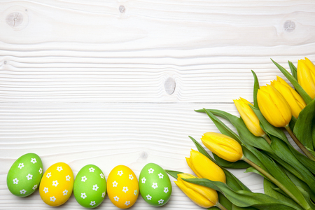Easter eggs and yellow tulips on white wooden background.
