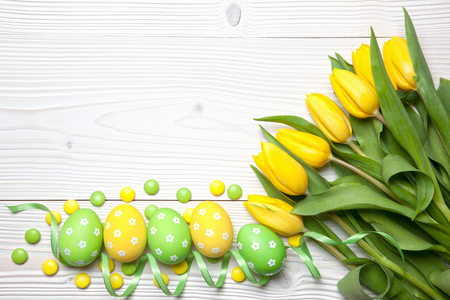 Easter eggs, chocolate candies and yellow tulips on white wooden background. Archivio Fotografico