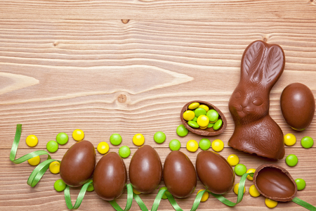 Easter chocolate eggs, bunny and candies on wooden background. Archivio Fotografico